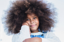 Positive African American Female Teenager With Afro Hairstyle Dressed In Casual Denim Overall Looking At Camera