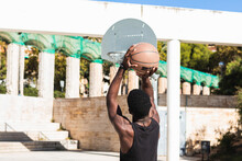 Back View Of Unrecognizable African American Male Athlete Playing Basketball On Court In Summer And Looking At Camera