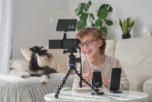 Cheerful Youtuber Boy Filming Video At Home And Taking Notes.