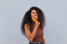 Positive African American Female With Curly Hair Wearing Yellow Protective Mask Standing Near Urban Building In City During Coronavirus Pandemic And Looking At Camera