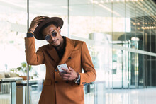 Front View Of Young Handsome Black Guy In Trendy Suit And Sunglasses Adjusting Hat While Standing In Modern Building Hall With Smartphone I Hand