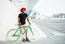 Confident African American Male In Trendy Clothes Standing With Modern Bike In Urban Area And Looking Away
