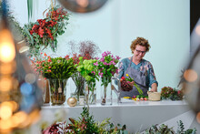 Cheerful Female Florist In Apron Making Bouquet From Colorful Fresh Tulips While Working In Flower Shop