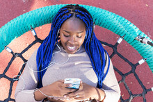 Top View Of Smiling African American Female Lying On Net Swing On Playground While Enjoying Songs In Earphones And Messaging On Smartphone At Weekend
