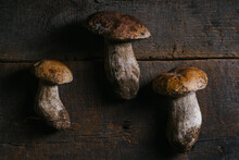 From Above Fresh Penny Bun Mushrooms On Wooden Table In Rustic Kitchen