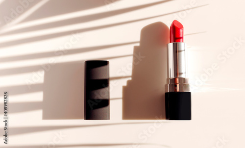 Red lipstick sun shadows from palm leaf on beige background flat lay top view copy space. Beauty and cosmetics background. Decorative cosmetics, makeup, women's lipstick, beauty brand product design © olgaarkhipenko