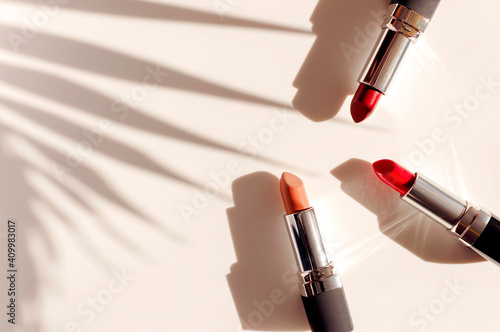 Fashion colorful lipsticks sun shadows from palm leaf on beige background flat lay top view. Beauty and cosmetics background. Decorative cosmetics makeup women's lipstick beauty brand product design © olgaarkhipenko