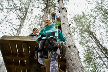 From Below Girl With Safety Harness Climbing Towards Platform With Sister And Father In Adventure Park In Forest