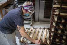 High Angle Side View Of Female Worker In Mask And Shield Making Notches On Loaves Of Baguette Dough While Preparing Pastry For Baking