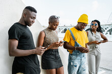 Young Black People In Stylish Clothes Standing In Urban Area And Messaging On Social Media Via Smartphones