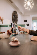 Cropped Unrecognizable Female Seller Standing At Counter And Holding Terminal While Customer Paying With Credit Card Using NFC Technology In Confectionery Cafe
