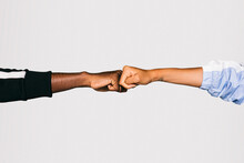 Close-up Of A Man's Black Fist Bumping Into A White Woman's Fist Over White Background