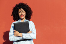 Cheerful Ethnic Businesswoman With Folder With Documents Standing On Street Near Orange Wall And Looking At Camera