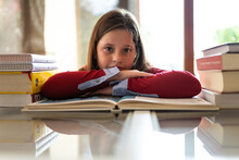 Cute Diligent Girl Sitting At Table Leaning On Arms Near Pile Of Textbooks And Looking At Camera While Doing Homework Assignment