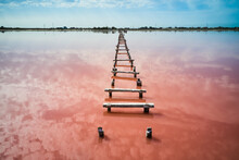 Drone View Of Old Wooden Walkway Leading Through Pink Water Of Calm Lake Towards Distant Coast