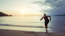 Back View Of Unrecognizable Professional Swimmer In Swimsuit And Cap Ready For Running In Sea Water During Training At Seaside At Sunset