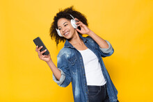 Cheerful Young African American Hipster Female In Denim Shirt Having Fun And Enjoying Loud Music Through Wireless Headphones On Bright Yellow Background