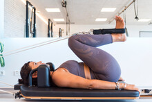 Side View Of Fit Woman Doing Legs Exercise With Resistance Ropes On Pilates Reformer In Gym