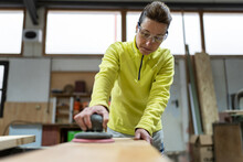 Low Angle Of Professional Mature Female Master In Casual Clothes And Goggles Polishing Wooden Plank Using Random Orbital Sander In Joinery