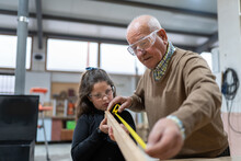 Adorable Little Girl In Casual Clothes And Goggles Helping Grandfather Measuring Wooden Board With Tape During Work In Manufacture