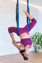 Adult Female Doing Frog Pose And Stretching Back On Aerial Ribbons While Practicing Yoga In Studio