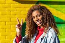 Optimistic Young Black Female Millennial With Curly Hair In Stylish Clothes Showing Gesture With Fingers And Smiling While Looking At Camera Against Yellow Wall