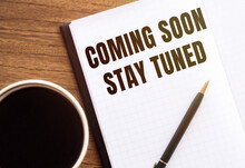 COMING SOON STAY TUNED. Text On Notepad On Wooden Desk.