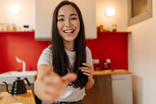 Brown-eyed Girl Touches Her Hair And Reaches For Camera. Woman Posing In Kitchen