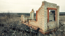 Destroyed And Burnt Brick Structure With A Window At The Edge Of The Field