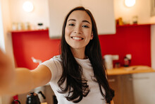 Woman In Great Mood Takes Selfie In Kitchen. Portrait Of Brown-eyed Girl