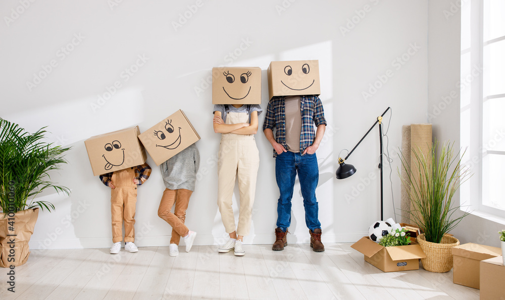 Fototapeta Family in funny carton boxes standing in new flat