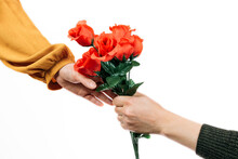 Hand Of A Man Giving A Bouquet Of Red Flowers To A Woman