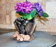 Purple Ornamental Flowers In A Clay Brown Vase