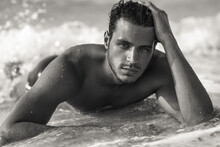 Portrait Of Sexy Handsome Topless Male Model With Beautiful Eyes Laying In The Ocean Water On The Beach. Black And White.