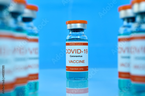 Canvas-taulu Covid-19 vaccine in bottles on blue table.