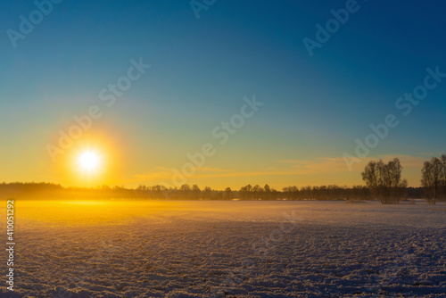 Fotografija Sunrise in winter over an agricultural area with snow in Germany,Sun appears bri