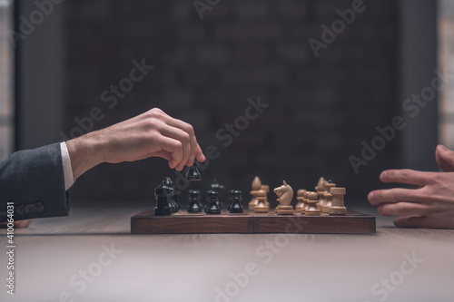 Foto Players hand with black pawn over chessboard