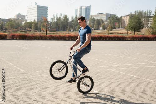Obraz na plátně Teenage BMX rider is performing tricks in skatepark