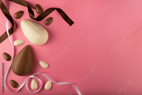 Easter. Composition with chocolate Easter eggs on pink background, space for text.