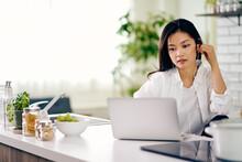 キッチンでノートパソコンを見る30代女性