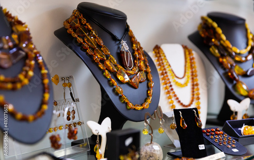 Various natural amber necklaces, earrings and pendants in glass case of jewelry Fototapeta