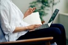 ノートパソコンでオンラインショッピングをする女性