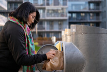 Woman Putting Paper Bag Into Recycling Bin