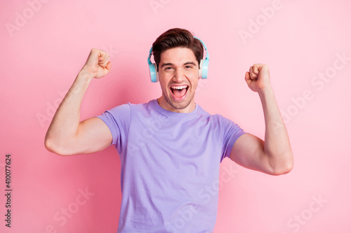 Photo of astonished carefree person fists up open mouth celebrate favorite track isolated on pink color background