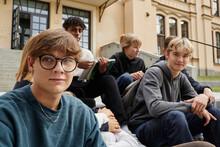 Teenagers Sitting In Front Of School