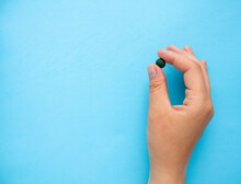 The Hand Holds One Chlorella Tablet. Blue Background. Selective Focus.