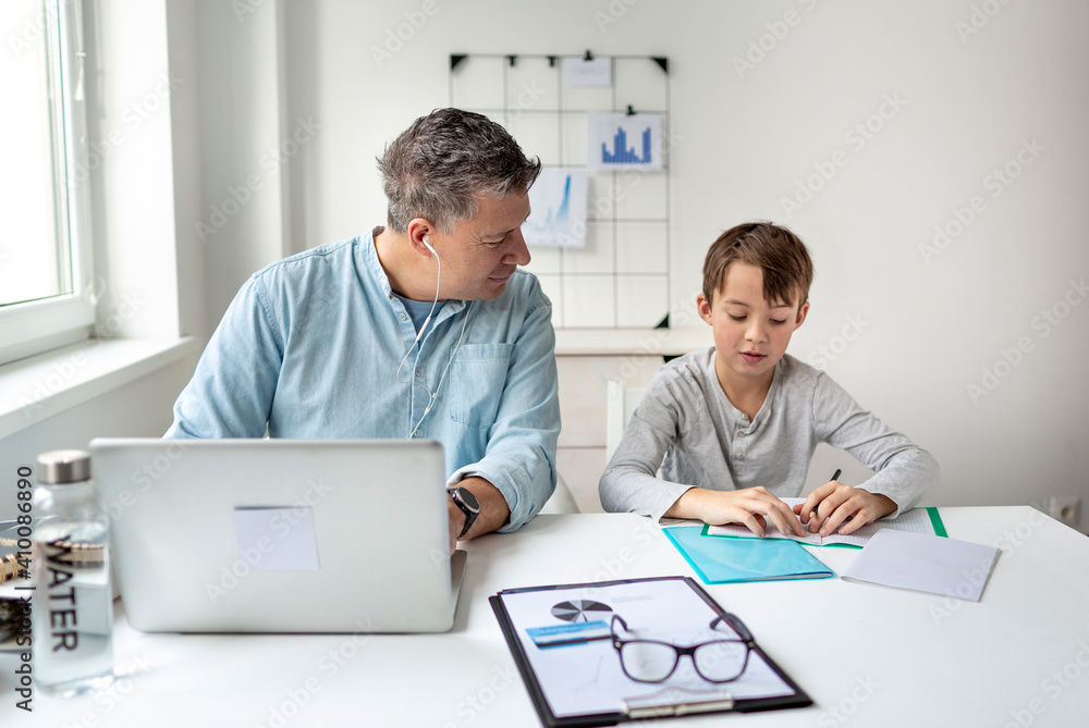 Fototapeta Business man works from home doing homeoffice and his son has homeschooling during corona crisis