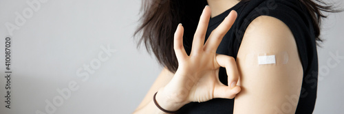 Healthy asian woman getting vaccinated immunity giving ok hand sign to rolling o Fototapete