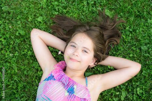 Papel de parede Young girl relaxing on a green clover meadow