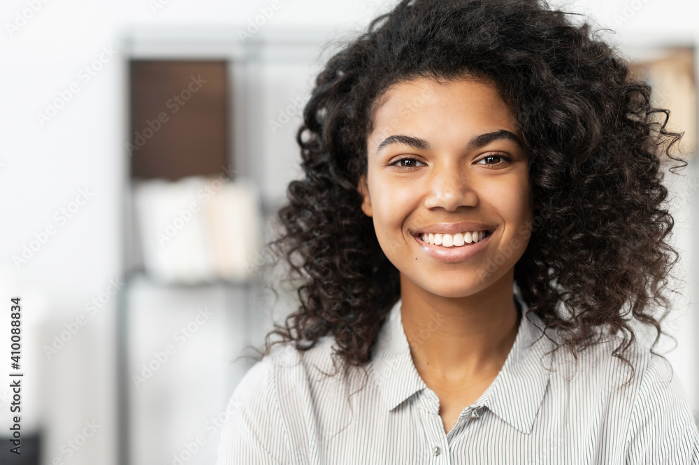 Fototapeta Headshot of a young elegant African American ethnic female with Afro curly hairstyle, beautiful smile and looking at the camera while standing against blurred home or office interior background